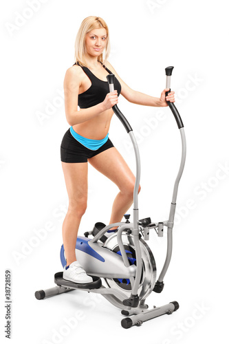 Beautiful woman exercising on a cross trainer machine