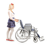 Full length portrait of a young girl pushing a wheelchair