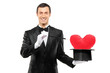 Magician holding a magic wand and top hat with a red heart shape
