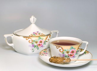 Antique crockery with tea and sugar stick