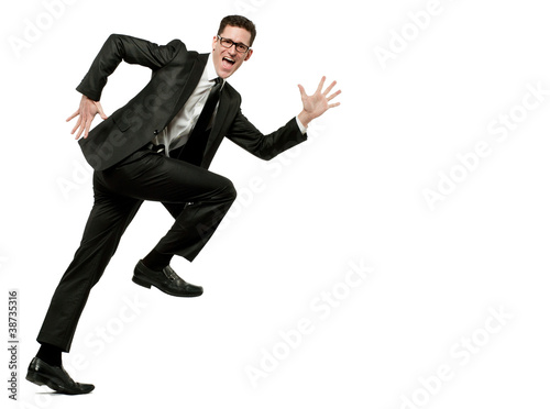 Happy businessman runs in black suit on white.