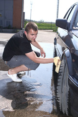 young man washing a car