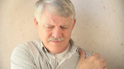 older man massages his painful shoulder