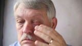 older man checks his bloodshot eyes