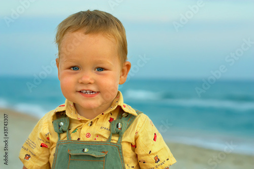 close-up portrait of adorable smiling baby boy standing near the