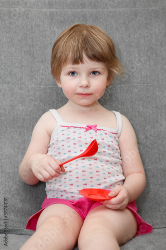 Portrait of small girl playing with spoon and plate toys