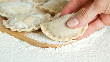 Dumplings in flour on the wooden board