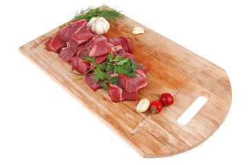 fresh uncooked beef meat slices over wooden cutting board