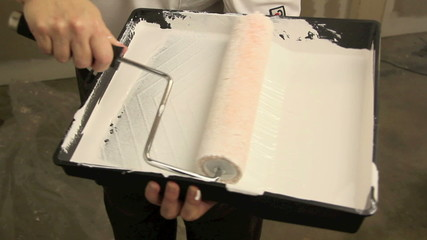 Dipping paint roller into tray and painting a wall
