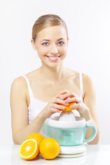 Girl with a juicer and oranges on a gray