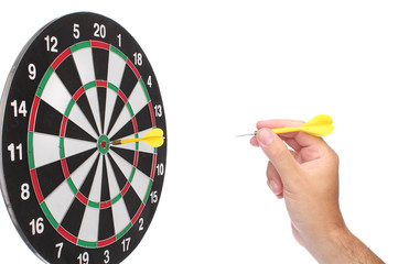 Hand throwing a yellow dart over white