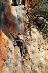 Rear view of rock climber battling his way up