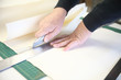 man cutting art paper with ruler and box cutter