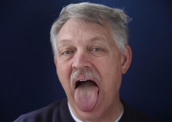older man showing his tongue