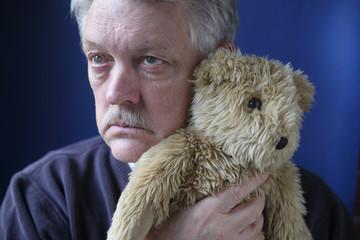 senior man holding teddy bear