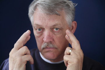 senior man crossing his fingers