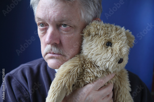senior man holding teddy bear