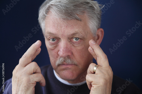 senior man crossing his fingers