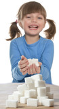little girl with sugar cubes on white background