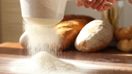 Hand sifts the flour through a sieve, slow motion