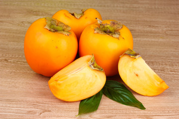 Appetizing persimmons on wooden background