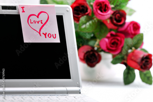 "Sticker ""I Love You"" on a laptop and flowers."