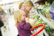 mother and daughter in fruit and vegetables section in supermark