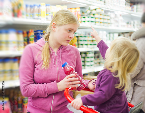 mother and daughter in fresh drinks section in supermarket