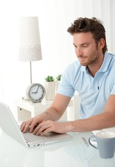 Handsome man typing on laptop computer