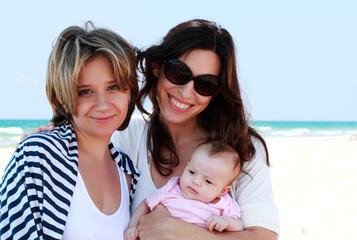 two beautiful girls with a baby on the beach