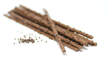 Chocolate sticks with chocolate granules on white background