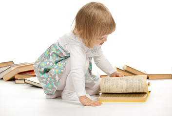 The little girl sitting among books