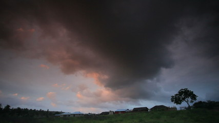 African landscape with rain clouds over a village.