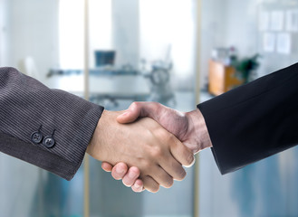 Business handshake in over a blurred office background