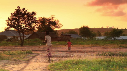 Children looking at the camera in Kenya at sunset.