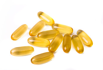 Transparent yellow pills on white background