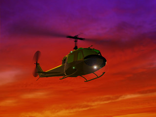 Flying helicopter UH-1and red sunset