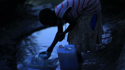 Girl filling a bucket with water near a village in Kenya.