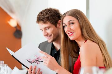 Paar schaut in die Speisekarte eines Restaurants