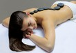 Model in a massage studio with hot stones on the back