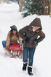 Two cute teenage girls with sledges having fun