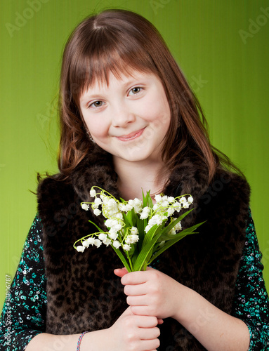little girl on green background. girl with flowers.