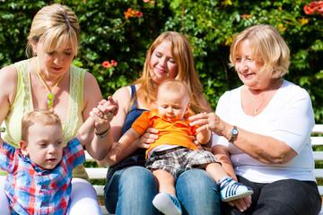 Zwei Mütter mit Großmutter und Kindern im Park