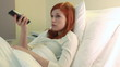 Young red-haired woman watching tv in hospital