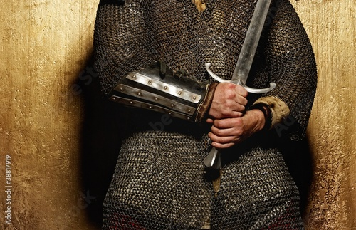 Knight holding sword on golden background.