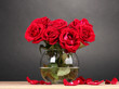 Beautiful red roses in vase on wooden table on gray background