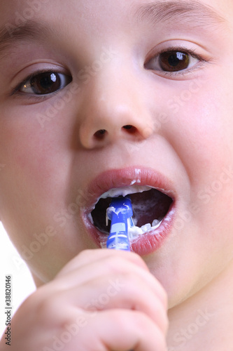 An adorable little boy brushing his teeth on white background