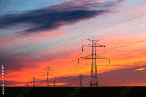 Transmission towers on the hills at red sunset