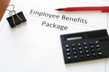 employee benefits package with calculator and pen