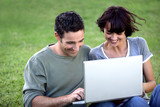 Couple sat with laptop in the park